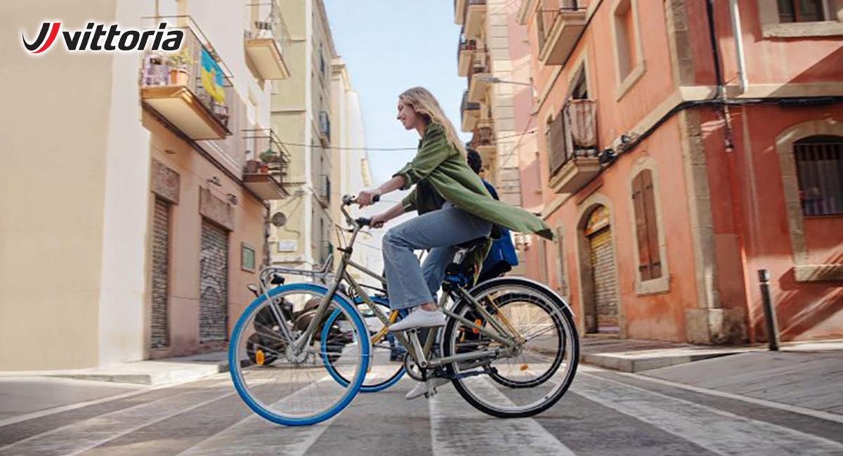 Una ragazza pedala in sella alla sua bici per le vie di una città