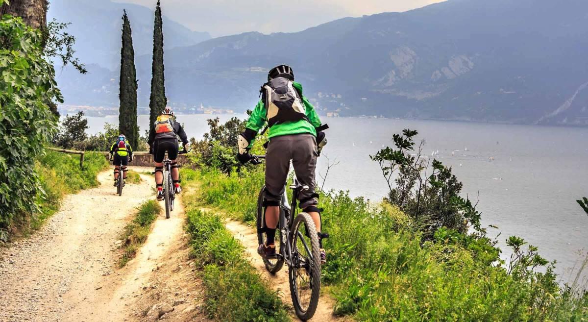 Dei cicloturisti pedalano con le mountainbike su uno sterrato con vista sul lago