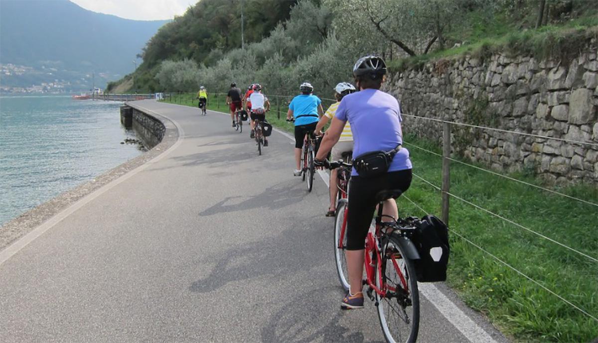 Dei cicloturisti in fila su una strada con vista lago