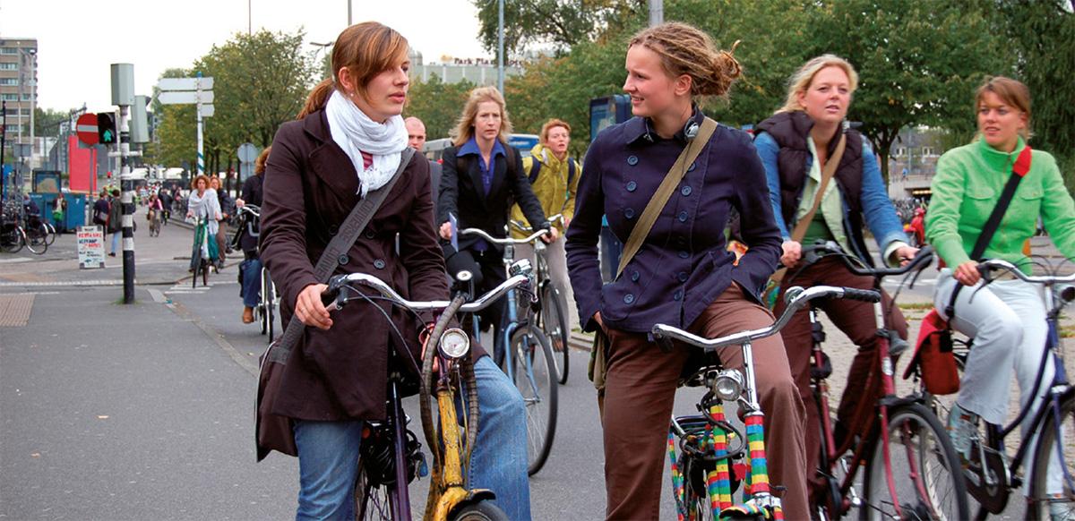 Delle giovani donne in sella alle proprie bici per le strade olandesi