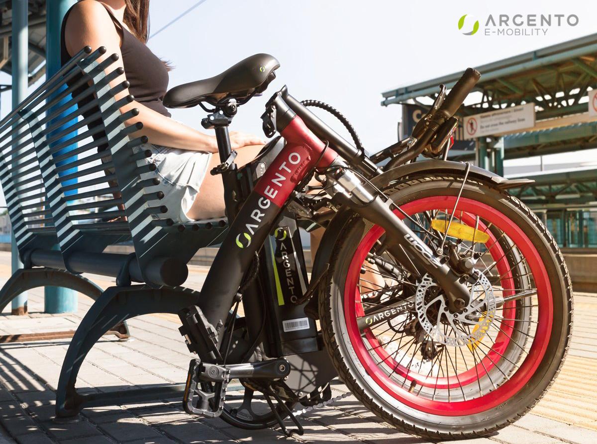 Una ragazza aspetta il treno in stazione accanto alla propria ebike pieghevole Argento Bike