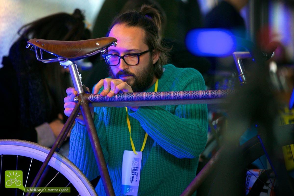 Danilo mentre applica il suo prodotto su una bicicletta