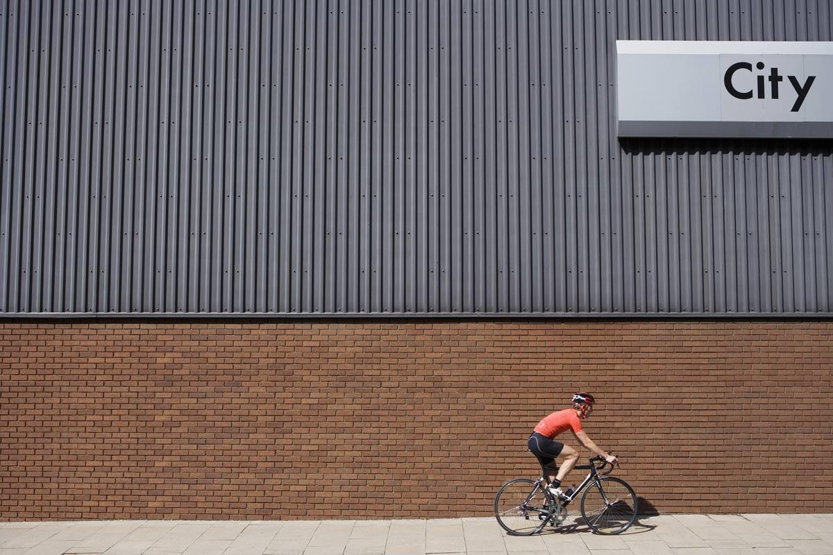 Un ciclista solitario a fianco di un palazzo nella City londinese