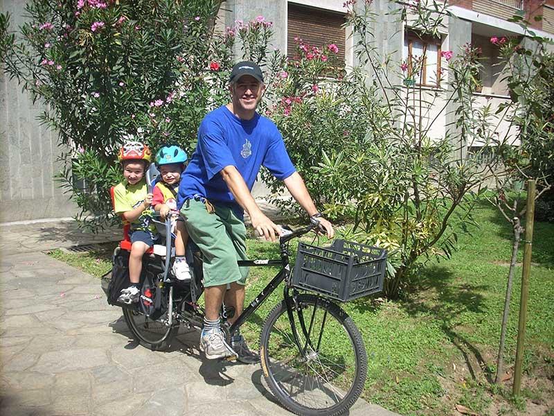 Padre sorridente in bicicletta con due bambini a bordo
